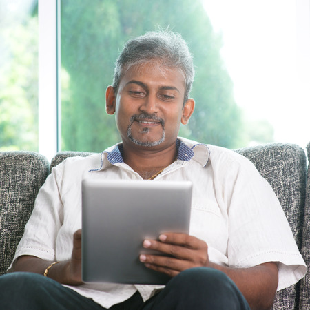 Portrait of middle aged Indian man reading on digital tablet computer and smiling at home.