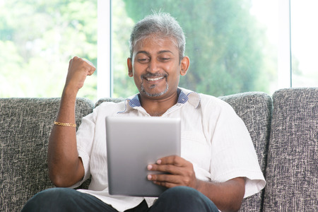 Portrait of middle aged Indian man reading on digital tablet computer and cheering at home.