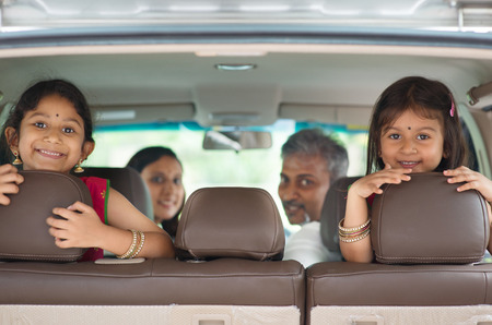 Happy Indian family sitting in car smiling, ready to vacation.  Asian parents and children. photo