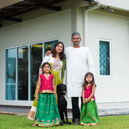 Beautiful Asian Indian family portrait smiling and standing outside their new house with pet dog. photo