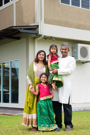 Beautiful Asian Indian family portrait smiling outside their new house. photo