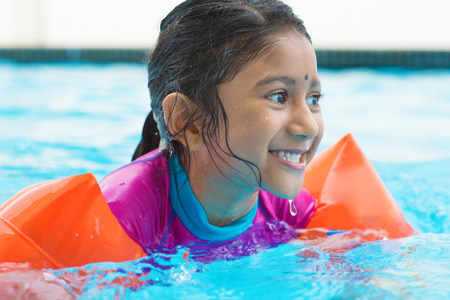 Indian girl learning swimming in pool. Asian child in swimmer class with float bands. Stock Photo