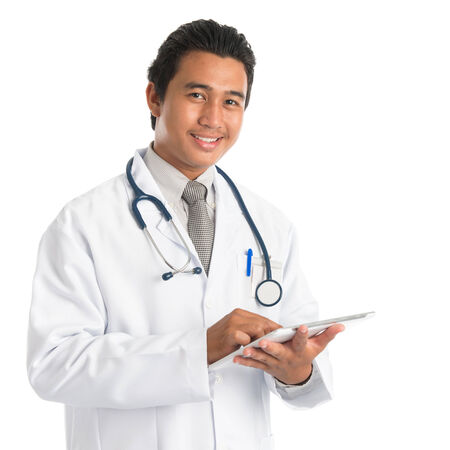 Portrait of southeast Asian male medical doctor using digital tablet computer, standing isolated on white . Young man model. photo