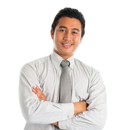 Portrait of handsome Asian young man in casual business attire, smiling confidently with arms crossed, standing isolated on white . photo