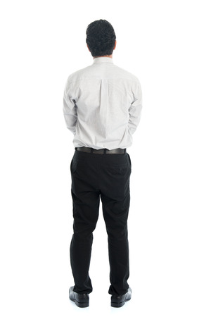 Full body rear view of Asian young male in casual business attire, standing isolated on white . photo