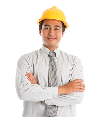 malay boy: Close-up of an Asian young man wearing a hardhat smiling and looking at camera, arms crossed standing isolated on white . Stock Photo