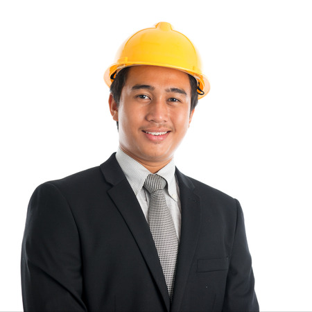 Close-up of an Asian young man wearing a hardhat smiling and looking at camera, standing isolated on white . photo