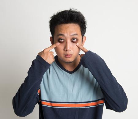 Aziatische man slapeloosheid, met grote ogen zak, op effen achtergrond