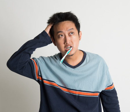 bedhead: Southeast Asian male scratching head and looking up while brushing teeth in a morning, on plain background