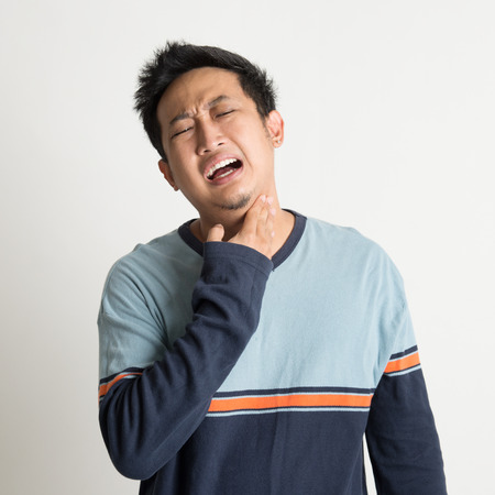 Asian male sore throat with painful face expression, on plain background photo