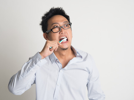 Asian business man woke up late, brushing teeth in hurry, on plain background Stock Photo