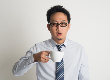 Tired Asian businessman with dark eyes circle holding coffee cup on plain background photo
