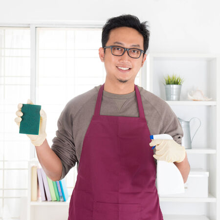 house chores: Asian man holding sponge and spray. House husband doing house chores, with interiors. Stock Photo