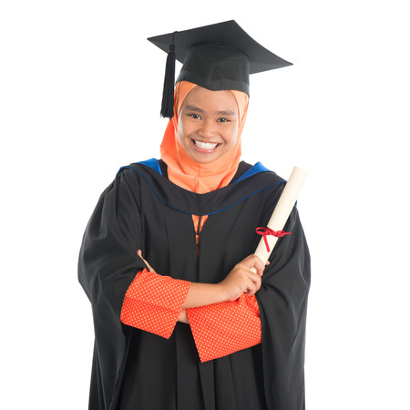 portrait of full length smiling asian female muslim student in  portrait of smiling asian female muslim student in graduate gown showing graduation diploma standing isolated on