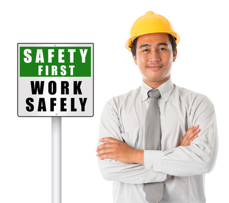 safety hat: Asian male worker wearing a hardhat smiling and looking at camera, arms crossed standing beside safety first sign board, isolated on white background. Stock Photo