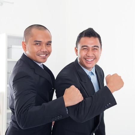 peleaba: Los hombres de negocios del sudeste asi�tico que celebra �xito en la Oficina. Foto de archivo