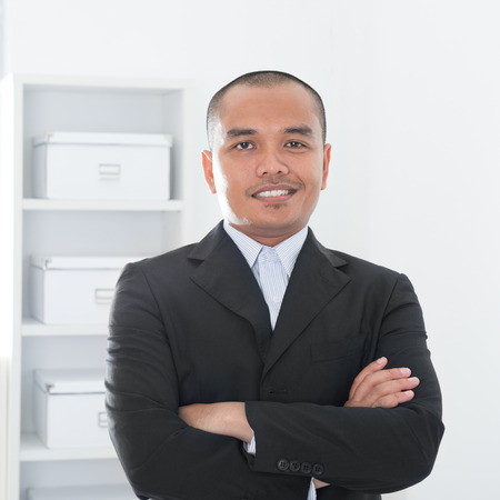 Portrait of 30s Asian Muslim business man smiling, real modern office background. Stock Photo