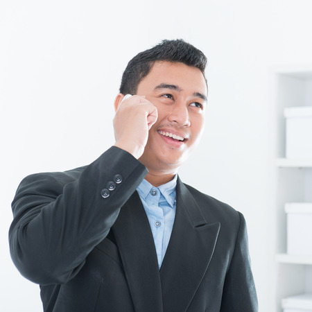 Southeast Asian business executive talking on smartphone in office background.