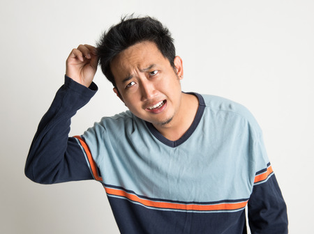 Asian man with bad hairstyle, on plain background photo