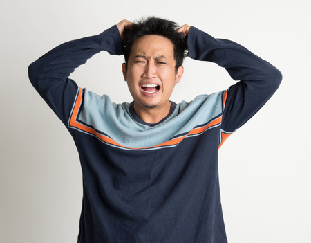 bad hair day: Portrait Of Mad Asian Man Pulling His Hair On Plain Background