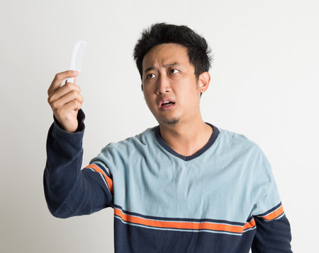 Southeast Asian man checking on a comb with shock facial expression, on plain background. photo