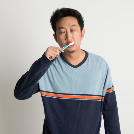 Sleepy Southeast Asian male brushing teeth while eyes closing in a morning, on plain background photo