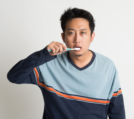 Southeast Asian male brushing teeth with sleepy eyes in a morning, on plain background photo
