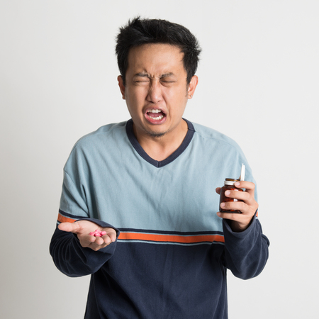 Asian male holding medicine bottle while sneezing, on plain background Stock Photo - 30173624
