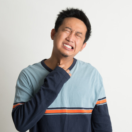 Asian man sore throat with painful face expression, on plain background photo