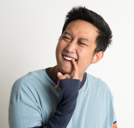 dientes sucios: Nasty hombre asiático retrato, algo atorado en los dientes, la excavación a mano, en el fondo plano
