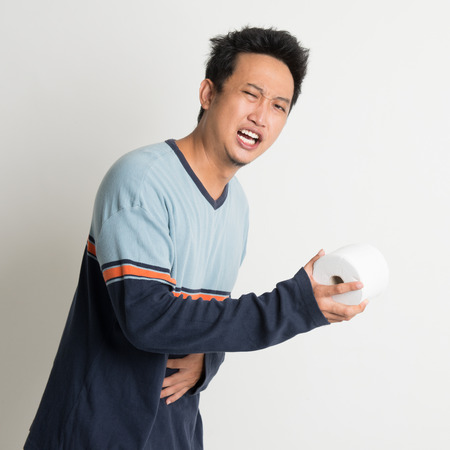 man stomach ache: Asian male stomach pain holding toilet paper running to toilet, with painful face expression, on plain background