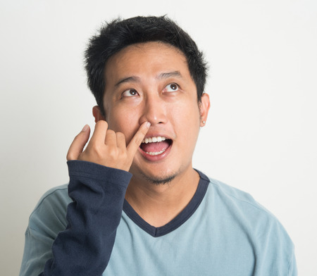 stupid body: Disgusting Asian man picking nose with eyes looking up, on plain background