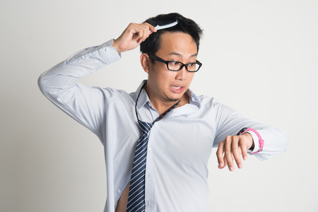 bedhead: Asian businessman combing hair in morning in hurry, checking time on watch, on plain background. Stock Photo