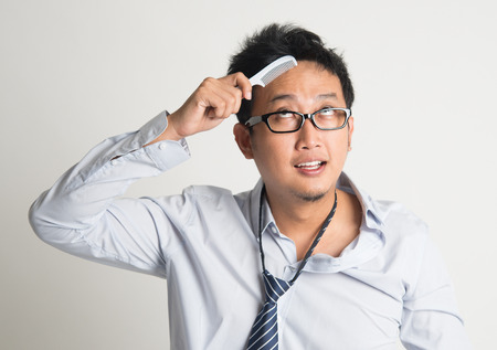 bedhead: Asian businessman combing hair in morning in hurry, on plain background