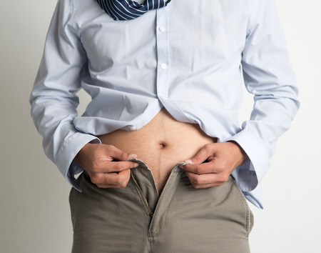 Middle age man with big belly unable to close the pants due to gaining weight, on plain background. Stock Photo