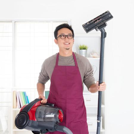 Asian man holding vacuum. House husband doing house chores, house interior.
