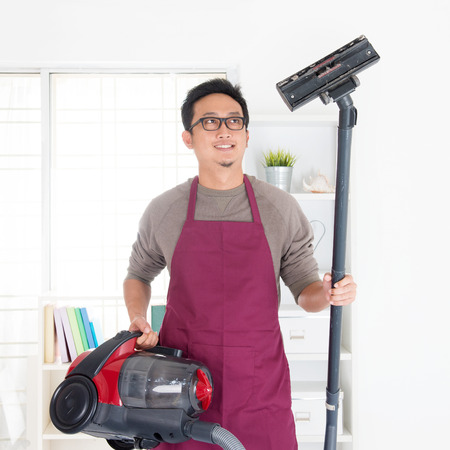 Asian man holding vacuum. House husband doing house chores, house interior.