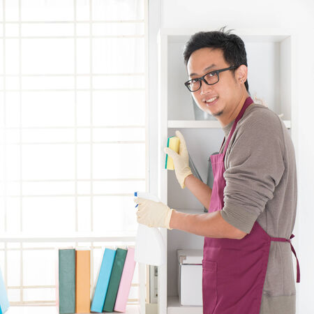 house chores: Asian man housekeeping. House husband doing house chores, with home interiors. Stock Photo