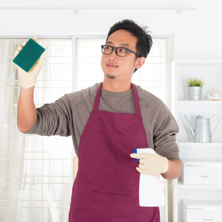 house chores: Asian guy housekeeping. House husband doing house chores, with home interiors. Male model.