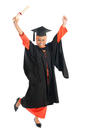 Portrait of full length smiling Asian female Muslim student in graduate gown hands raised showing graduation diploma jumping isolated on white background.