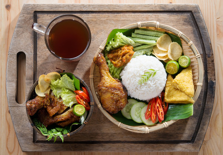 traditional: Famous traditional Indonesian food. Delicious nasi ayam penyet with sambal belacan. Fried chicken rice and tea with overhead view. Stock Photo
