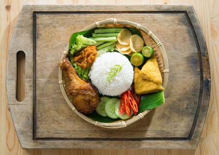 indonesian food:  Delicious nasi ayam penyet with sambal belacan. Fried chicken rice with overhead view. Famous traditional Indonesian food. Stock Photo
