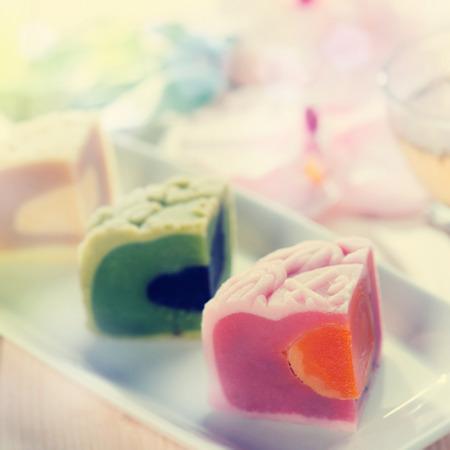 Pasteles de luna de la piel de la nieve de colores en un plato blanco con la taza de té. Mediados de los alimentos chinos Festival de Otoño. Foto de archivo - 30690424