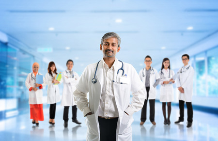 indian: Multiracial diversity Asian medical team, expertise senior and mature doctors leading young practitioners, standing inside hospital.