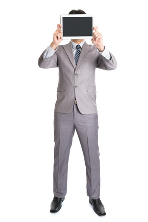 Full body Asian businessman hand holding digital computer tablet covering his face, standing isolated on white background. photo