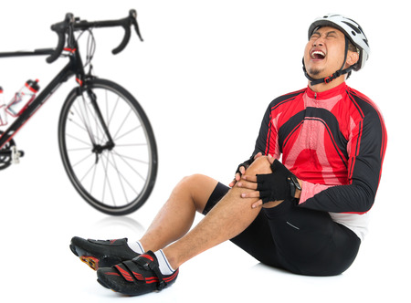 crash helmet: Asian cyclist fell down from bike with injured knee joint, painful facial expression and sitting on floor, isolated on white background.