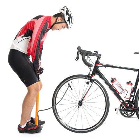 air pressure: Asian cyclist pumping air to bike tire, using manual air-pump, isolated on white background. Stock Photo