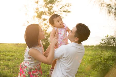 actividades recreativas: Retrato de la alegre familia asiática feliz jugando juntos en el parque al aire libre durante la puesta del sol de verano. Foto de archivo