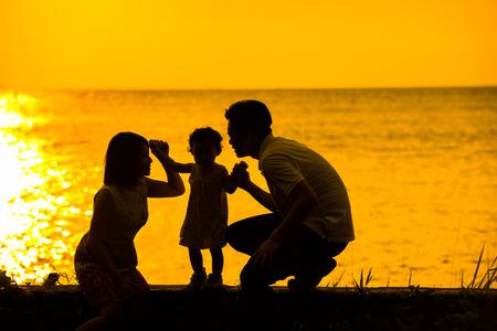 familias jovenes: Silueta de la familia asiática feliz jugando en la playa al aire libre durante la puesta del sol de verano.