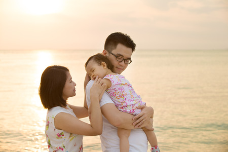 Portrait of young Asian family outdoor beach vacation, during summer sunset, natural sunlight.  Stock Photo
